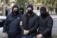 Plain-clothed policemen escort handcuffed well-known actor and director Dimitris Lignadis, center, to a magistrate's office in Athens, Sunday, Feb. 21, 2021. Lignadis, 56, the former artistic director of Greece's National Theatre, has been arrested on rape charges, police say. (AP Photo/Yorgos Karahalis)