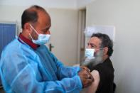 A health worker vaccinates a Palestinian man against the coronavirus disease (COVID-19), in Gaza City