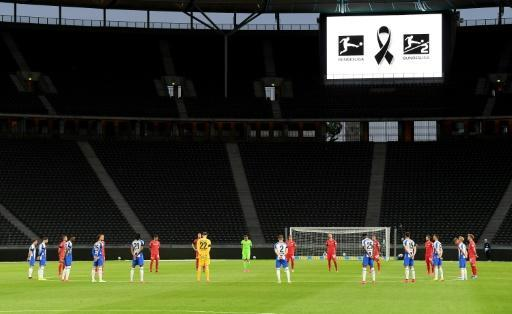 Players observe a minute of silence to commemorate the victims of the coronavirus pandemic ahead of the Berlin derby