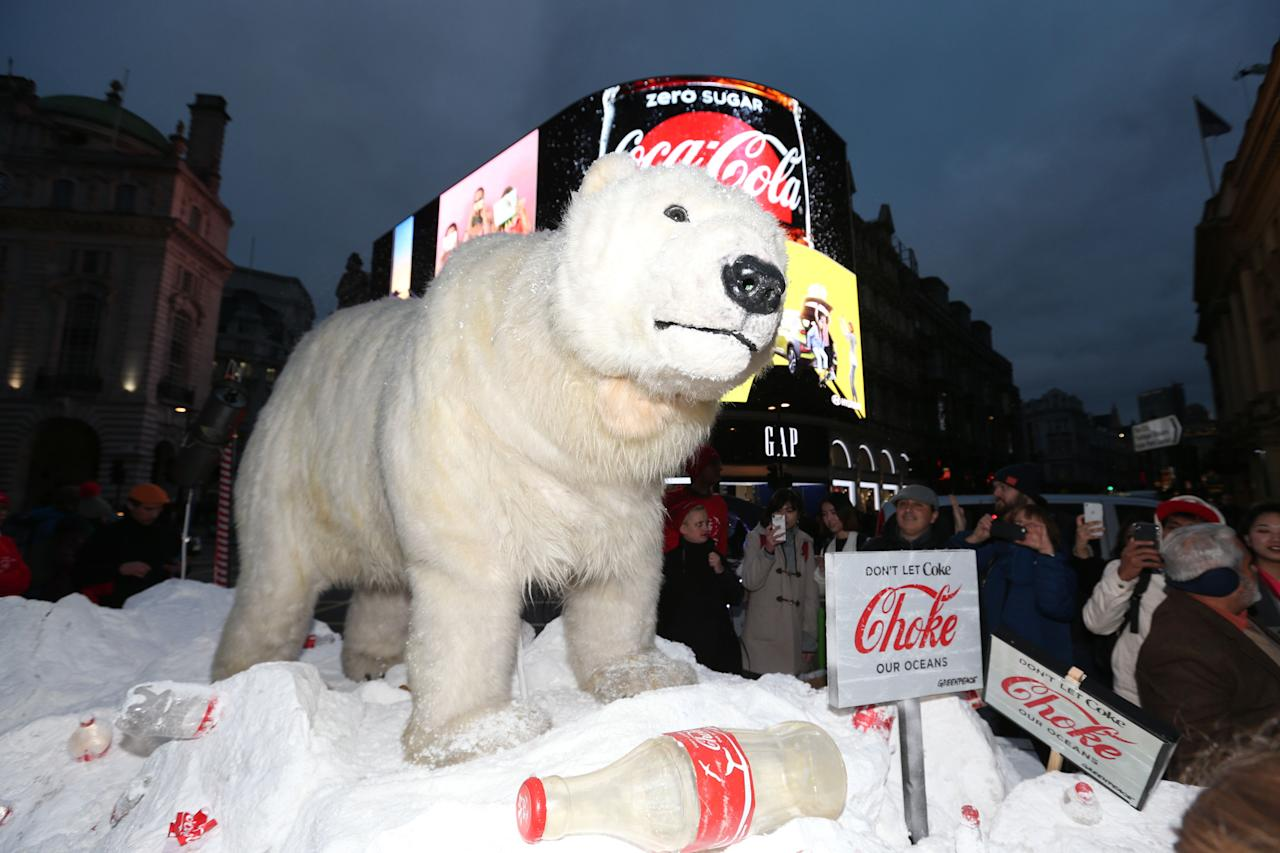 <p>Members of the public look at a Greenpeace ice float with Paula, a polar bear puppet, and empty Coca Cola bottles in Piccadilly Circus, central London as the environmental group calls on the drinks manufacturer to reduce their plastic footprint. (PA) </p>
