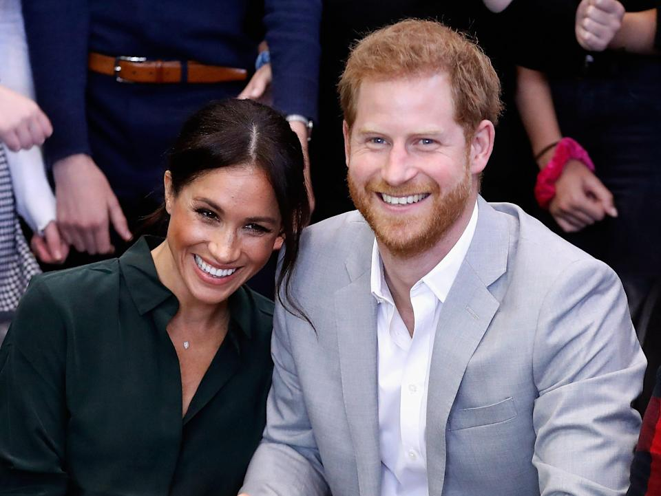 Meghan Markle and Prince Harry smile and lean into each other in 2018.