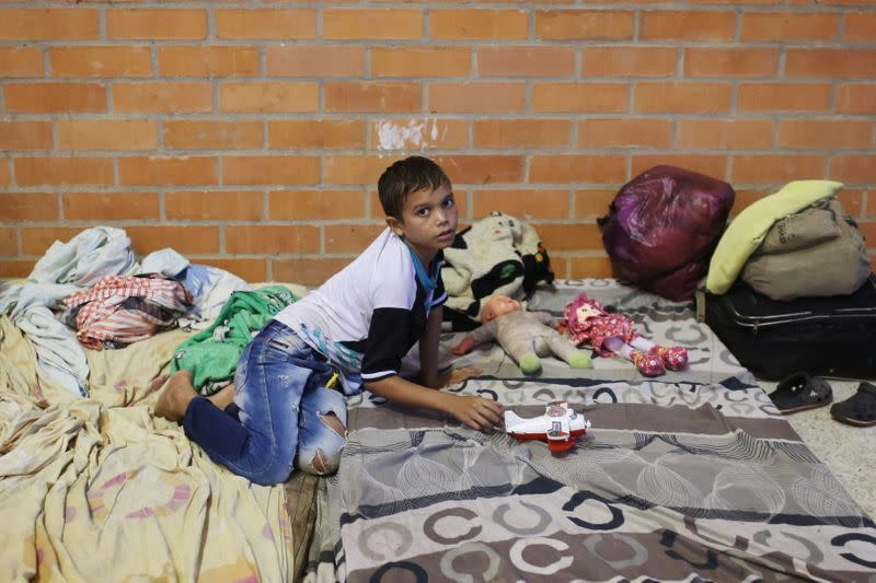 A Venezuelan migrant child plays inside a coliseum where a temporary camp has been set up, after fleeing his country due to military operations, according to the Colombian migration agency, in Arauquita