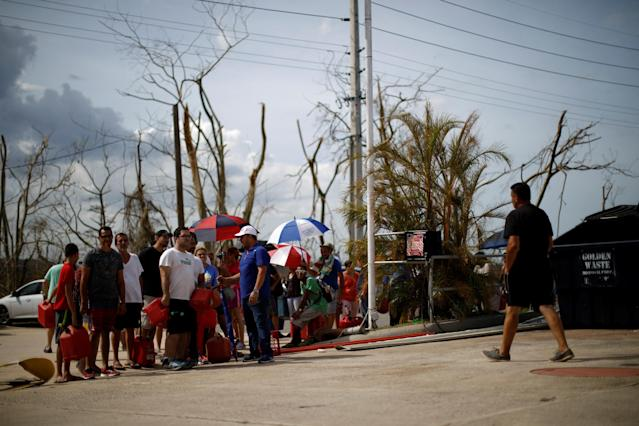 People queue to fill containers with gasoline at a gas station after the area was hit by Hurricane Maria in Toa Baja, Puerto Rico. (Carlos Garcia Rawlins / Reuters)