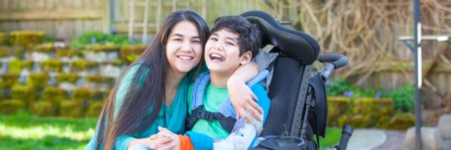 woman hugging a child in a wheelchair and smiling