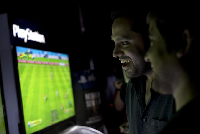People play video games during the FIFA Interactive World Cup 2014 Grand Final at Sugar Loaf, Rio de Janeiro, Brazil, Thursday, July 3, 2014. The FIWC is organised by FIFA and its presenting partners, and is recognized by Guinness World Records as the world's largest online gaming tournament. (AP Photo/Silvia Izquierdo)