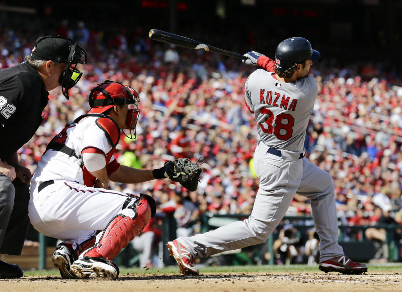 St. Louis Cardinals' Pete Kozma hits a three-run home run in the second inning of Game 3 of the National League division baseball series against the Washington Nationals on Wednesday, Oct. 10, 2012, in Washington. Watching behind the plate are home plate umpire Joe West and Nationals catcher Kurt Suzuki. (AP Photo/Alex Brandon)
