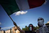 A man waves an Italian flag during a protest against the government restriction measures to curb the spread of COVID-19, in Rome, Saturday, Oct. 10, 2020. (AP Photo/Andrew Medichini)