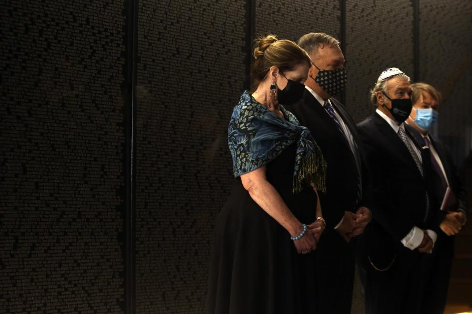 U.S. Secretary of State Mike Pompeo, second left, and his wife Susan, left, observe one minute of silence during their visit at the Jewish Museum in the northern city of Thessaloniki, Greece, Monday, Sept. 28, 2020. Pompeo said Monday the United States will use its diplomatic and military influence in the region to try to ease a volatile dispute between NATO allies Greece and Turkey over energy rights in the eastern Mediterranean. (AP Photo/Giannis Papanikos, Pool)