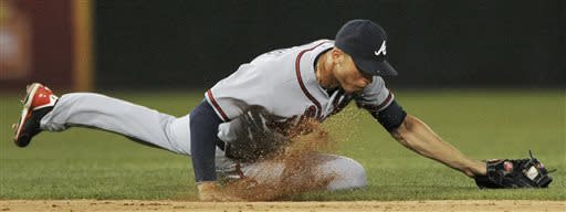 Atlanta Braves shortstop Andrelton Simmons stops a grounder by Chicago White Sox's Gordon Beckham before throwing him out at first base during the seventh inning of a baseball game in Chicago, Friday, July 19, 2013. (AP Photo/Paul Beaty)