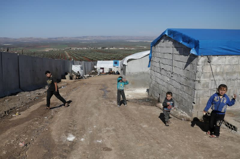 FILE PHOTO: Internally displaced Syrian children walk near the wall in Atmah IDP camp, located near the border with Turkey