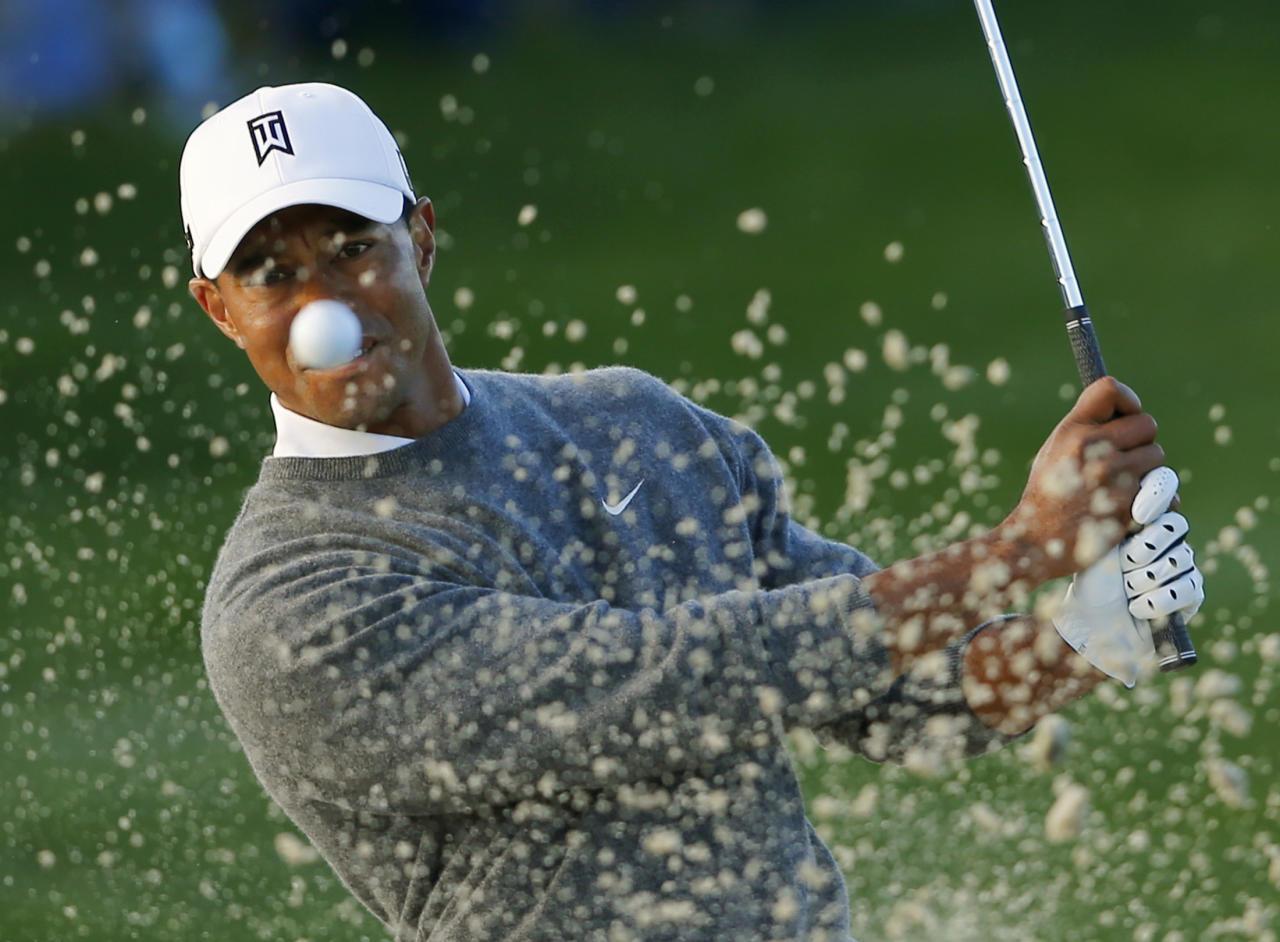 U.S. golfer Tiger Woods hits from a sand trap on the fifth hole during weather delayed fourth round play at the Farmers Insurance Open in San Diego, California January 27, 2013. REUTERS/Mike Blake  (UNITED STATES - Tags: SPORT GOLF TPX IMAGES OF THE DAY) - RTR3D2HO