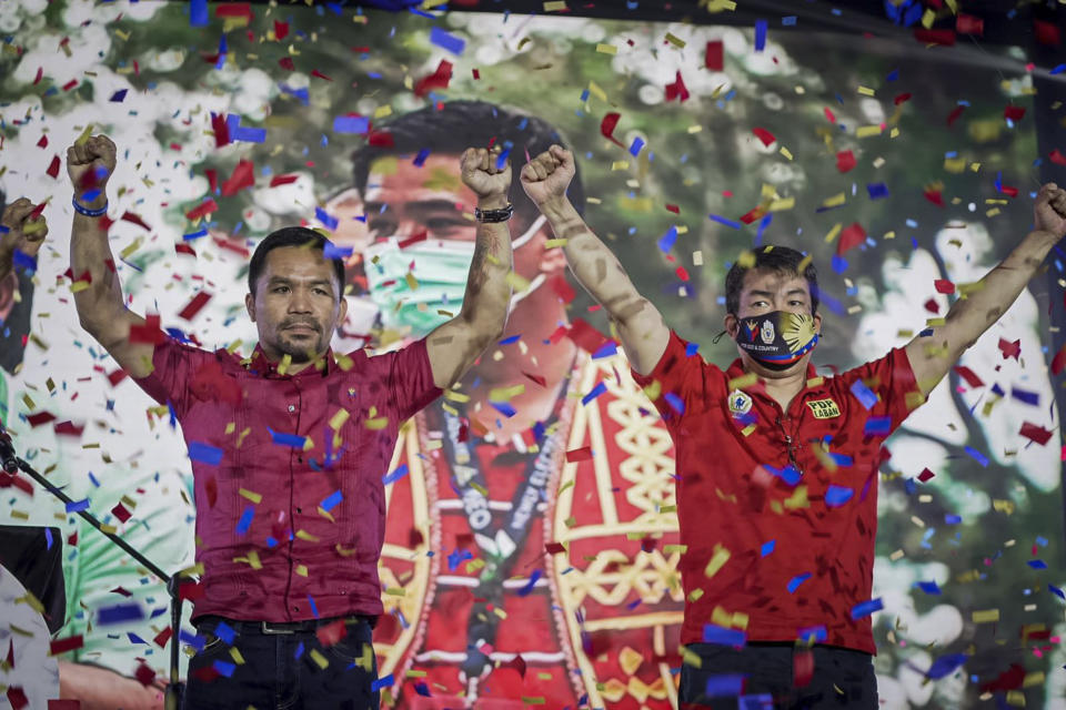 In this photo provided by the Manny Pacquiao MediaComms, Senator Manny Pacquiao, left, raises his hands during a national convention of his PDP-Laban party in Quezon city, Philippines on Sunday Sept. 19, 2021. Philippine boxing icon and senator Manny Pacquiao says he will run for president in the 2022 elections. (Manny Pacquiao MediaComms via AP)