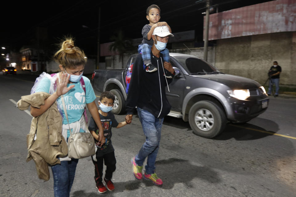 Migrants who aim to reach the U.S. walk along a highway as they leave San Pedro Sula, Honduras before dawn Tuesday, March 30, 2021. (AP Photo/Delmer Martinez)