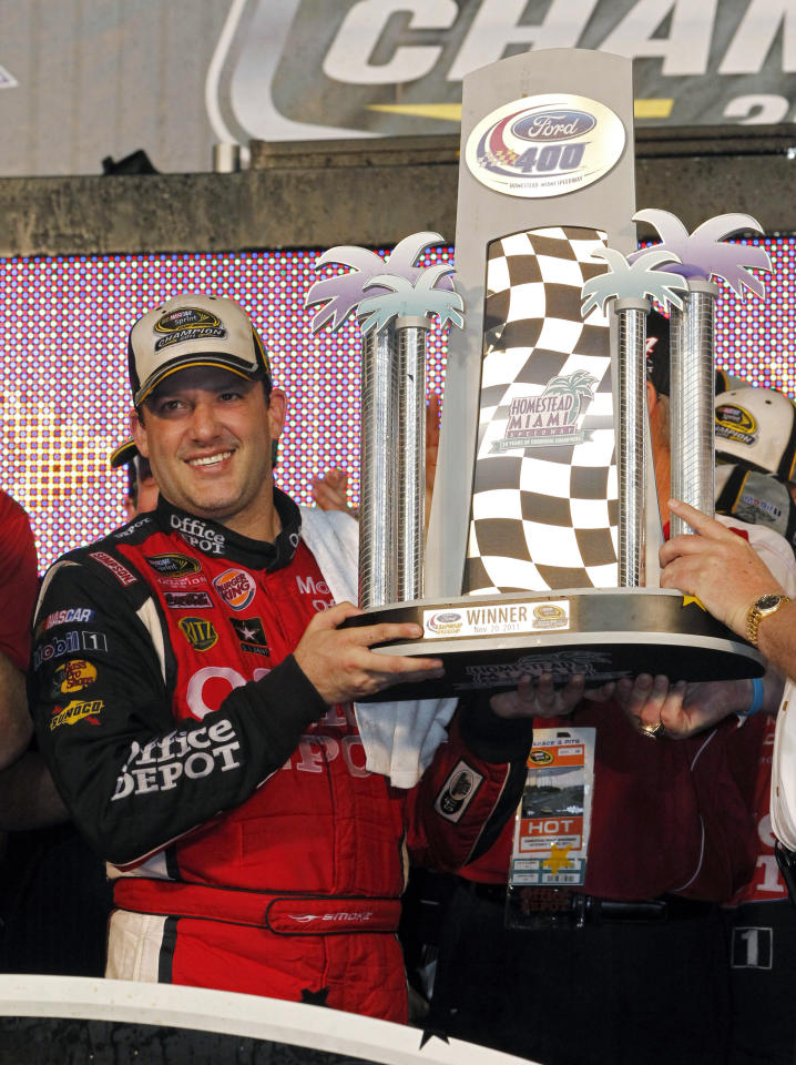Tony Stewart holds the trophy for winning the NASCAR Sprint Cup Series auto race at Homestead-Miami Speedway in Homestead, Fla., Sunday, Nov. 20, 2011. Stewart also won the series championship. (AP Photo/Terry Renna)