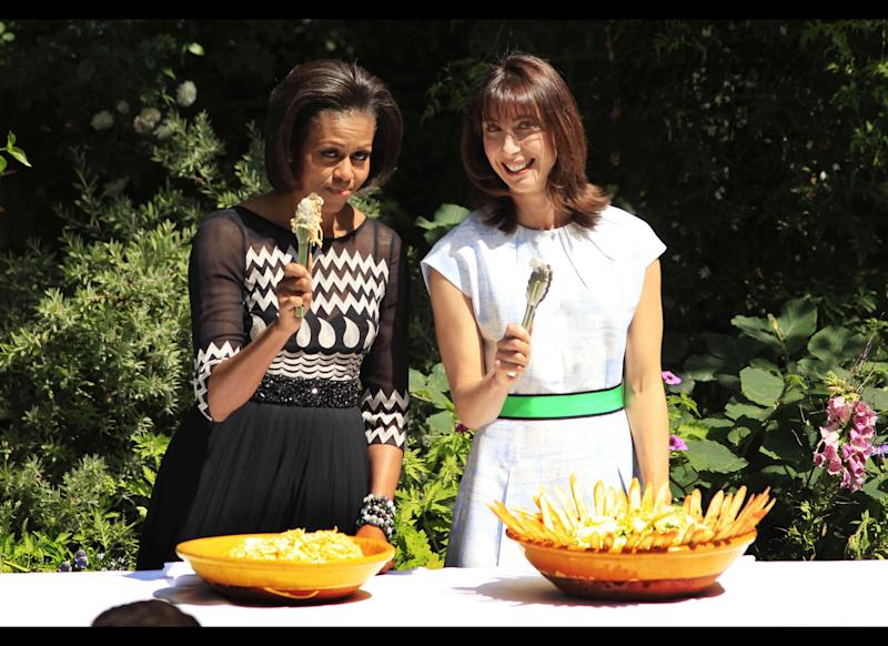 U.S. first lady Michelle Obama, left, and Samantha Cameron, the wife of Britain's Prime Minister David Cameron, hold up serving tongs towards the media as they serve food during a barbecue in the garden of 10 Downing Street in London, Wednesday, May 25, 2011. The barbecue Wednesday, where Cameron, U.S. President Barack Obama and their wives served food, was attended by members of the military from the UK and the U.S. (AP Photo/Matt Dunham-Pool)
