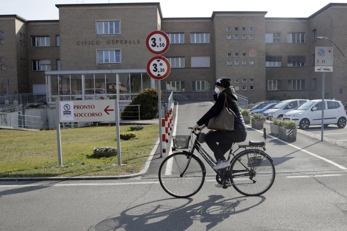 A woman wearing a mask rides past the Codogno hospital, Northern Italy, Saturday, Feb. 22, 2020. A dozen northern Italian towns were on effective lockdown Saturday after the new virus linked to China claimed two fatalities in Italy and sickened an increasing number of people who had no direct links to the origin of the virus. (AP Photo/Luca Bruno)