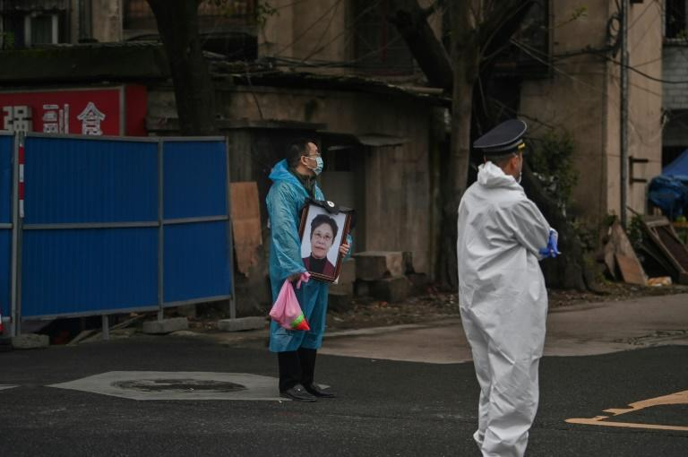 As small groups gathered quietly around gravesites on the hillside in Wuhan, a man draped in a blue plastic protective poncho stood silently near the cemetery entrance, holding a photo portrait of a woman who had died