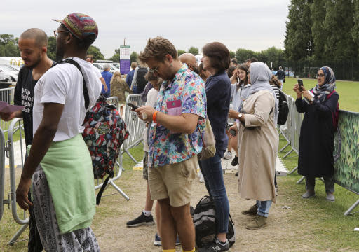 """In this Tuesday, July 9, 2019, tennis fans wait in a queue to get tickets to enter the Wimbledon Tennis Championships in London. For many the Wimbledon experience starts in a tent as they gather in a small park across from the tournament grounds to camp out, some for days, in the hope of getting a ticket to Centre Court as they are released each day. """"The Queue"""" is a decades-old tradition that has grown to become its own phenomenon.(AP Photo/Natasha Livingstone)"""