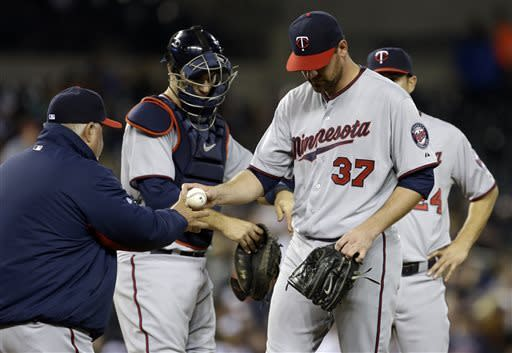 Minnesota Twins starting pitcher Mike Pelfrey (37) gives the ball to manager Ron Gardenhire during the sixth inning of a baseball game against the Detroit Tigers in Detroit, Monday, April 29, 2013. (AP Photo/Carlos Osorio)