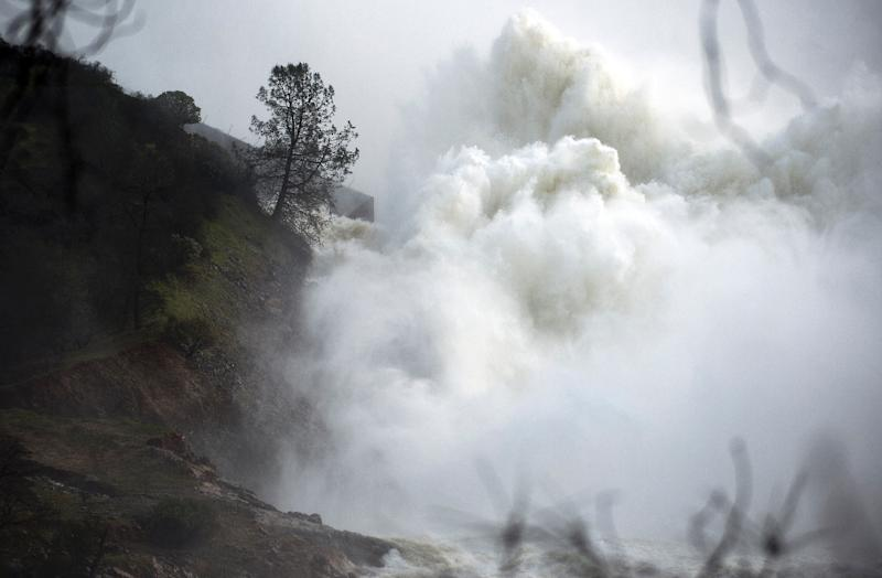 Water rushes down a spillway as an emergency measure at the Oroville Dam in Oroville, California on February 13, 2017