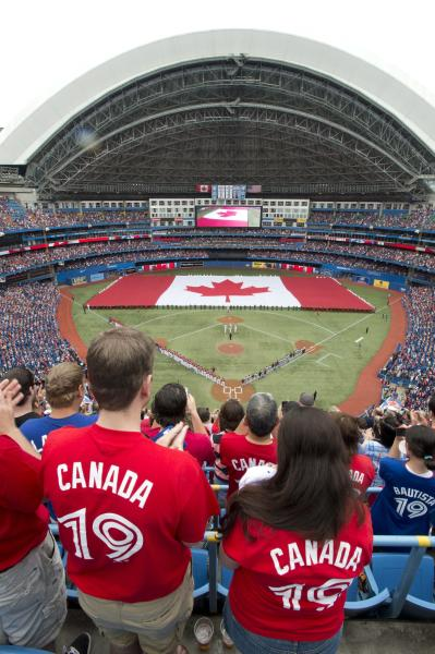 Toronto Blue Jays fans stand for the playing of the national anthems before a baseball game against the Detroit Tigers in Toronto, Monday, July 1, 2013. (AP Photo/The Canadian Press, Frank Gunn)