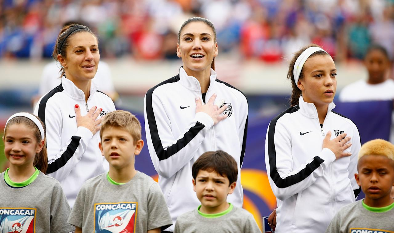 <p>(L-R) Carli Lloyd, #10, Hope Solo #1 and Mallory Pugh of the United States wait on the field prior to start of the game between the United States and Canada during the Championship final of the 2016 CONCACAF Women's Olympic Qualifying at BBVA Compass Stadium on February 21, 2016 in Houston, Texas. (Photo by Scott Halleran/Getty Images) </p>