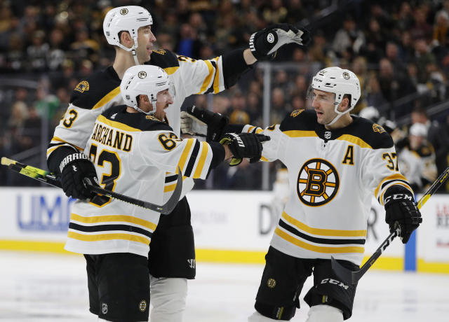 Boston Bruins left wing Brad Marchand (63) celebrates with teammates Zdenoa Chara, back left, and Patrice Bergeron after scoring against the Vegas Golden Knights during the third period of an NHL hockey game Wednesday, Feb. 20, 2019, in Las Vegas. (AP Photo/John Locher)