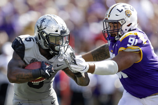 Vanderbilt running back Ke'Shawn Vaughn (5) tries to move past LSU defensive lineman Breiden Fehoko (91) in the first half of an NCAA college football game Saturday, Sept. 21, 2019, in Nashville, Tenn. (AP Photo/Mark Humphrey)