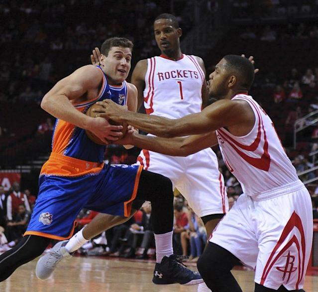 The Shanghai Sharks' Jimmer Fredette, left, drives against the Houston Rockets' Eric Gordon during an exhibition game on Oct. 2, 2016, in Houston. (AP)