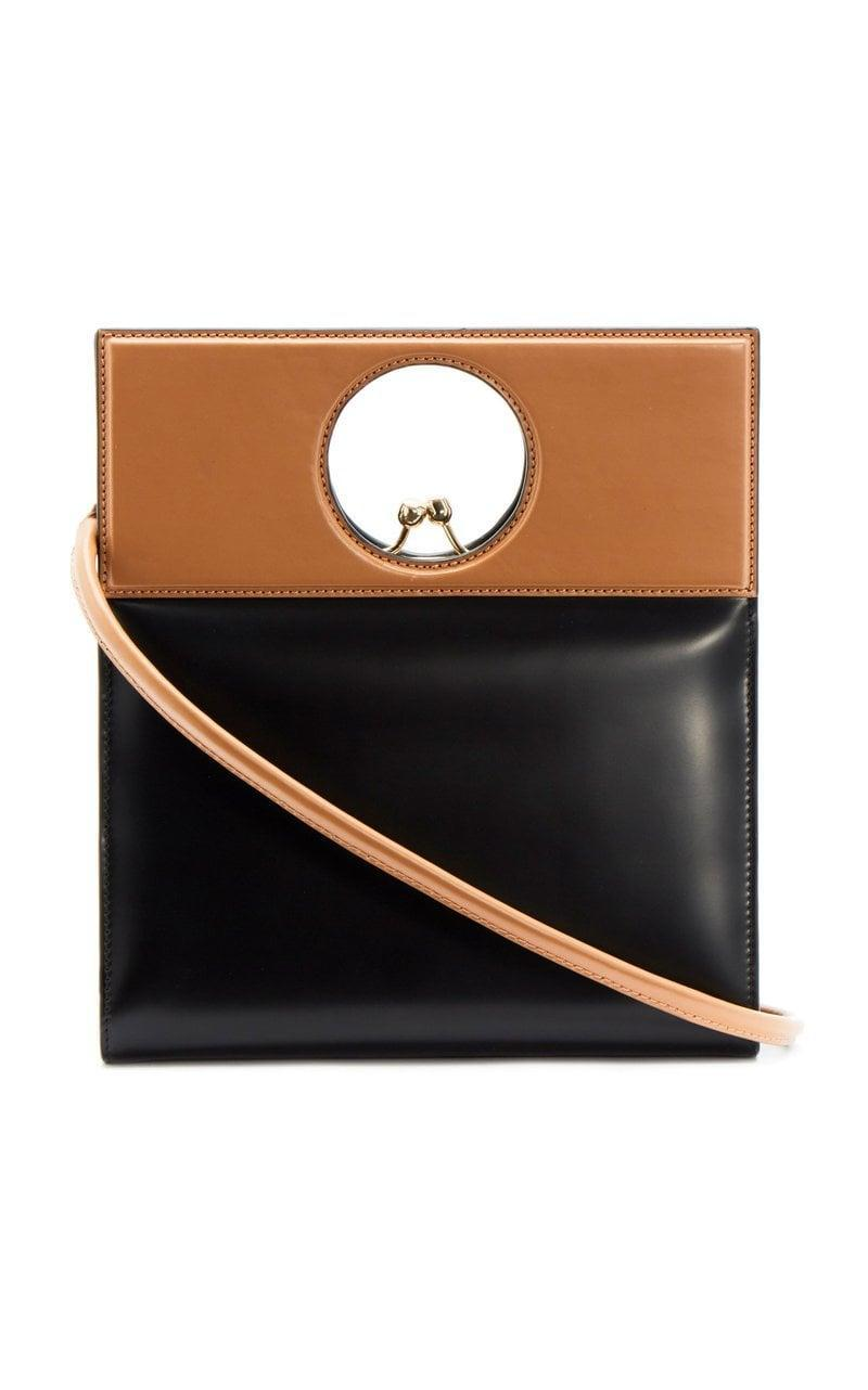 """<p>""""This sculptural bag from the new brand Usisi Sister is perfect for every day. The shape of the <span>Eddie Two-Tone Leather Top Handle Bag</span> ($825) is so modern and I love the hardware detail.""""</p>"""