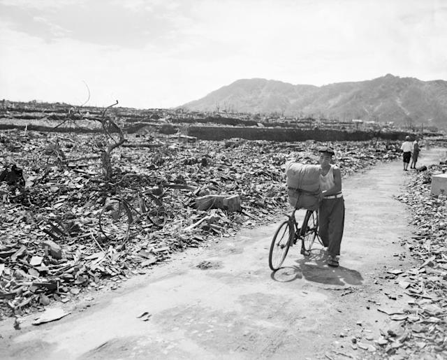 <p>A Japanese civilian pushes his loaded bike down a path which has been cleared of the rubble. On either side of the path debris, twisted metal, and gnared tree stumps fill the area in Nagasaki on Sept. 13, 1945. This is in the center of the devasted area. (Photo: Bettmann/Getty Images) </p>