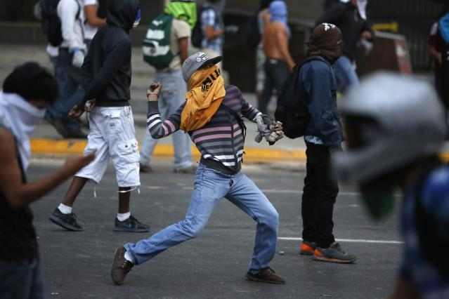 Anti-government protesters throw stones during a protest against Nicolas Maduro's government in Caracas March 7, 2014. Latin American foreign ministers will meet next week to discuss the unrest in Venezuela that has left at least 20 dead and convulsed the South American OPEC nation, diplomatic sources said on Friday. REUTERS/Carlos Garcia Rawlins (VENEZUELA - Tags: POLITICS CIVIL UNREST)