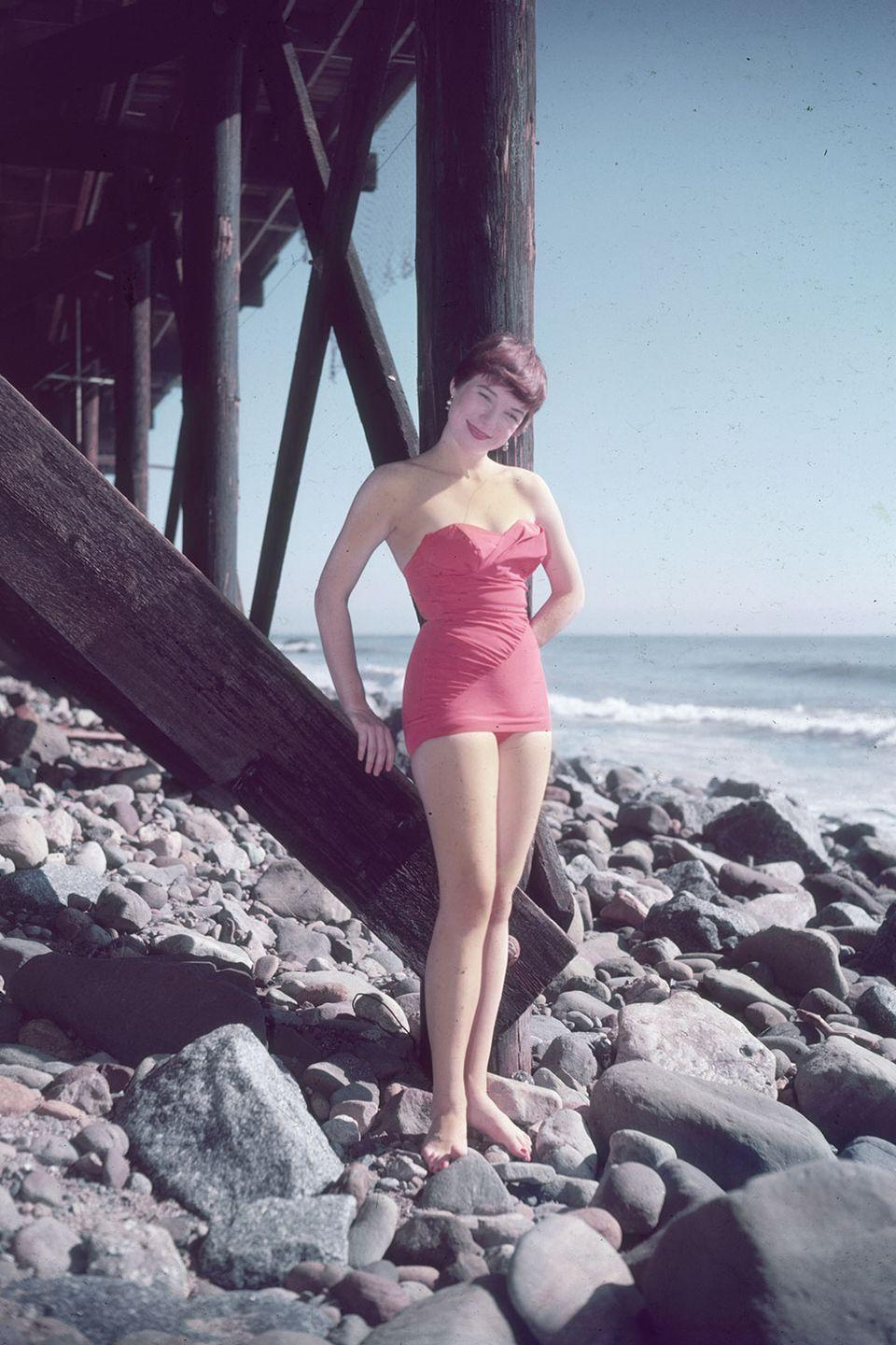 <p>Shirley MacLaine models her swimsuit while standing on the rocks under a pier, circa 1955.</p>