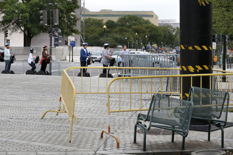 "In this photo taken Oct. 1, 2012, tourists on Segways pass dilapidated benches and fencing blocking a heating grate at John Marshall Park on Pennsylvania Avenue NW in Washington. Washington's Pennsylvania Avenue, sometimes called ""America's Main Street,"" is being listed among the nation's endangered landscapes because of neglect and deferred maintenance by the National Park Service. (AP Photo/Jacquelyn Martin)"