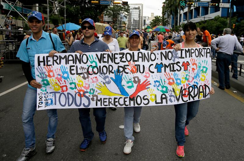 "In this May 1, 2013 photo, supporters of the opposition march with a banner that reads in Spanish; ""Venezuelan brother: The color of your shirt does not matter, we all deserve the truth,"" during a May Day march in Caracas, Venezuela. Husbands and wives, brothers and sisters, parents and children find themselves on opposite sides of the bitter fight between Nicolas Maduro, whose supporters tend to wear the color red, and an opposition that accuses the socialist government of using fraud and intimidation to win the presidency. (AP Photo/Fernando Llano)"
