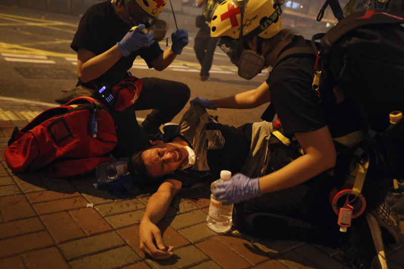 Medical workers help a protester in pain from tear gas fired by policemen on a street in Hong Kong, Sunday, July 21, 2019. Hong Kong police have thrown tear gas canisters at protesters after they refused to disperse. Hundreds of thousands of people took part in a march Sunday to call for direct elections and an independent investigation into police tactics used during earlier pro-democracy demonstrations. Police waved a black warning flag Sunday night before lobbing the canisters into a crowd of protesters. (Photo: Bobby Yip/AP)