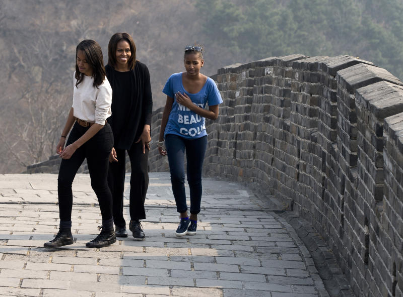 U.S. first lady Michelle Obama walks with her daughters Malia, left, and Sasha, right, as they visit the Mutianyu section of the Great Wall of China in Beijing Sunday, March 23, 2014. (AP Photo/Andy Wong)