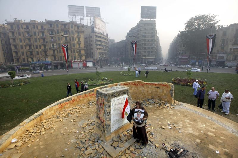 """A woman holds a poster of Egyptian Defense Minister Gen. Abdel-Fattah el-Sissi with an Arabic that reads, """"we authorize you,"""" as she stands at the foundation for a future memorial to protesters killed in the country's uprising more than two-and-a-half years of turmoil, after it was damaged in Tahrir Square, Cairo, Egypt, Tuesday, Nov. 19, 2013. Unknown assailants attacked, chipped away and sprayed graffiti on the huge stone early on Tuesday, just hours after it was inaugurated by the country's interim prime minister. (AP Photo/Amr Nabil)"""
