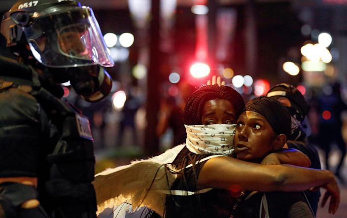 <p>SEPT. 21, 2016 — Two women embrace while looking at a police officer in uptown Charlotte, NC during a protest of the police shooting of Keith Scott, in Charlotte, North Carolina. (Jason Miczek/Reuters) </p>