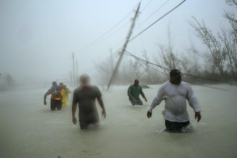 Volunteers walk under the wind and rain from Hurricane Dorian through a flooded road as they work to rescue families near the Causarina bridge in Freeport, Grand Bahama, Bahamas, Sept. 3, 2019. (Photo: Ramon Espinosa/AP)