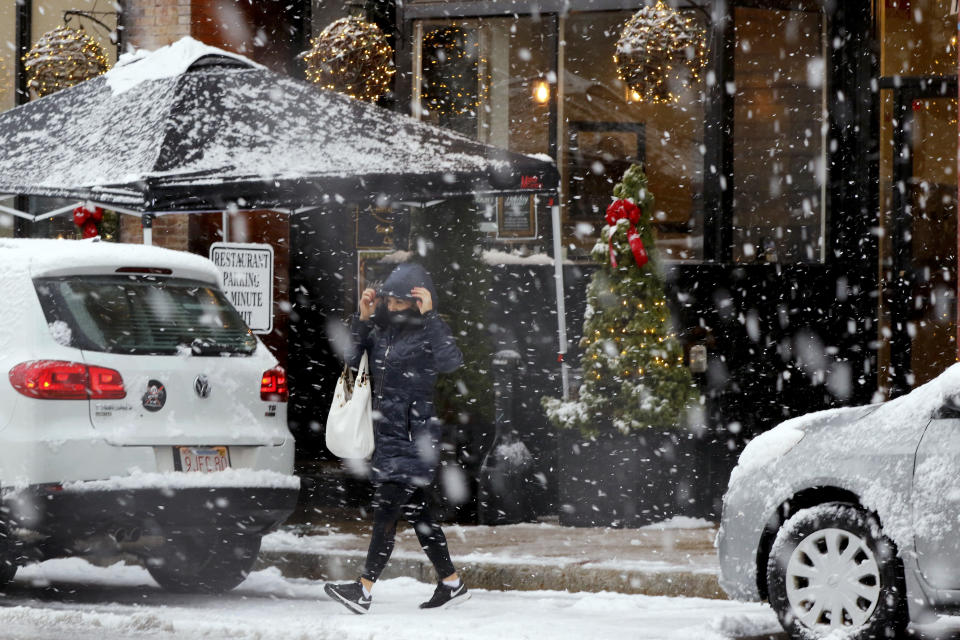 A woman crosses Main Streete during heavy snow, Saturday, Dec. 5, 2020, in downtown Marlborough, Mass. The northeastern United States is seeing the first big snowstorm of the season. (AP Photo/Bill Sikes)