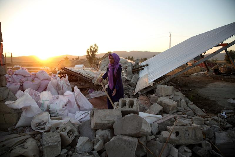 A woman struggles through the debris of a building in Kalaleh, Iran, on Tuesday, after a 7.3-magnitude earthquake Sunday. (Fatemeh Bahrami/Anadolu Agency via Getty Images)