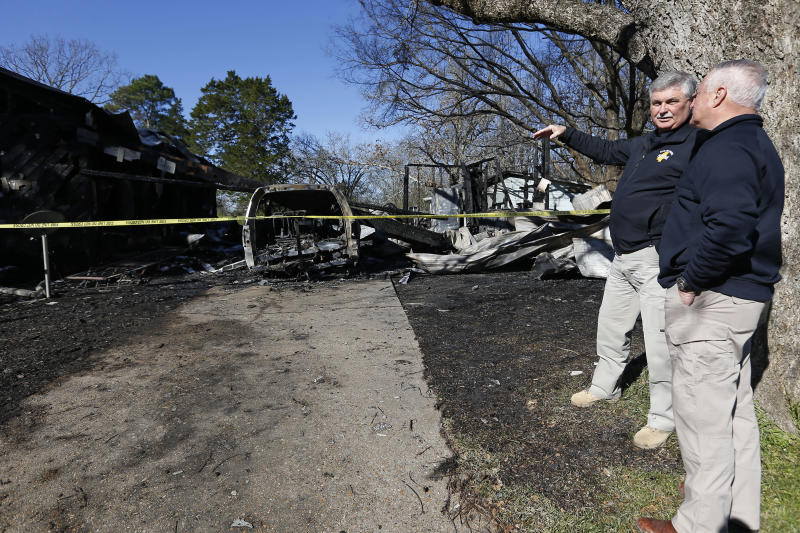Officials from the Mississippi Fire Marshal's office, confer outside the scene of a fatal fire on Saturday, Feb. 8, 2020 in Clinton, Miss.   Authorities say a mother and her six children have been killed in the house fire in central Mississippi.  (AP Photo/Rogelio V. Solis)
