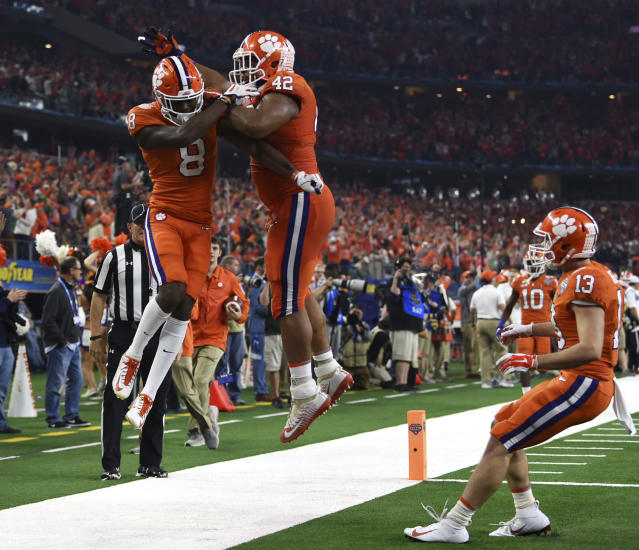 Clemson wide receiver Justyn Ross (8), defensive lineman Christian Wilkins (42) and wide receiver Hunter Renfrow (13) celebrates touchdown scored by Ross in the first half of the NCAA Cotton Bowl semi-final playoff football game against Notre Dame on Saturday, Dec. 29, 2018, in Arlington, Texas. (AP Photo/Jeffrey McWhorter)