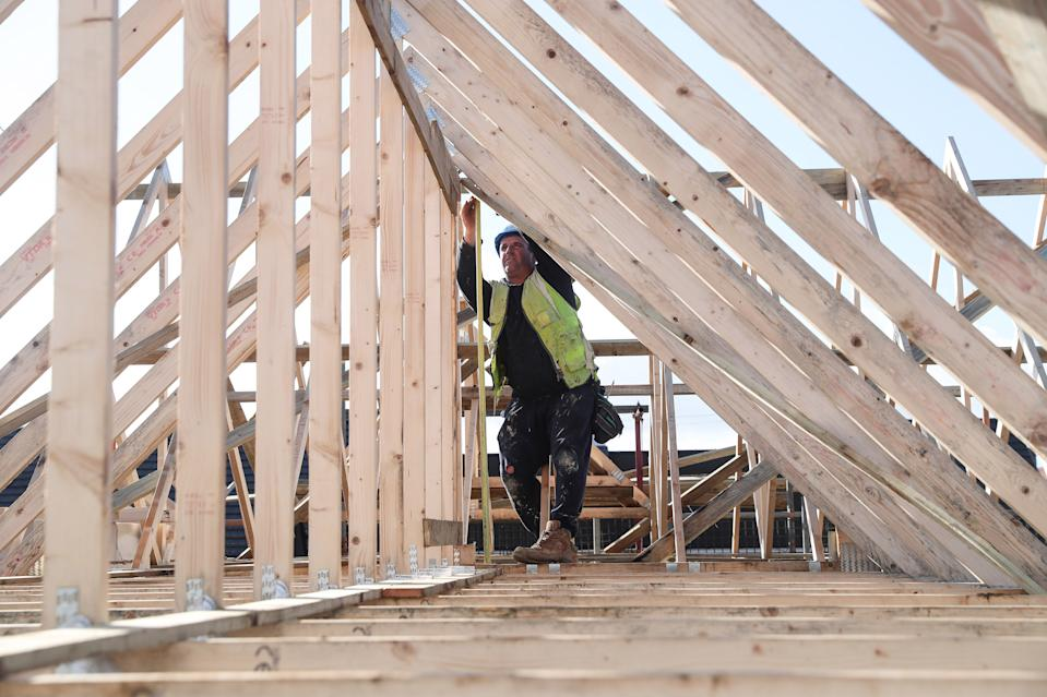 A builder working for Taylor Wimpey builds a roof on an estate in Aylesbury, Britain. Photo: Eddie Keogh/Reuters