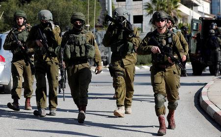 Israeli soldiers walk during clashes with Palestinians in Ramallah in the occupied West Bank