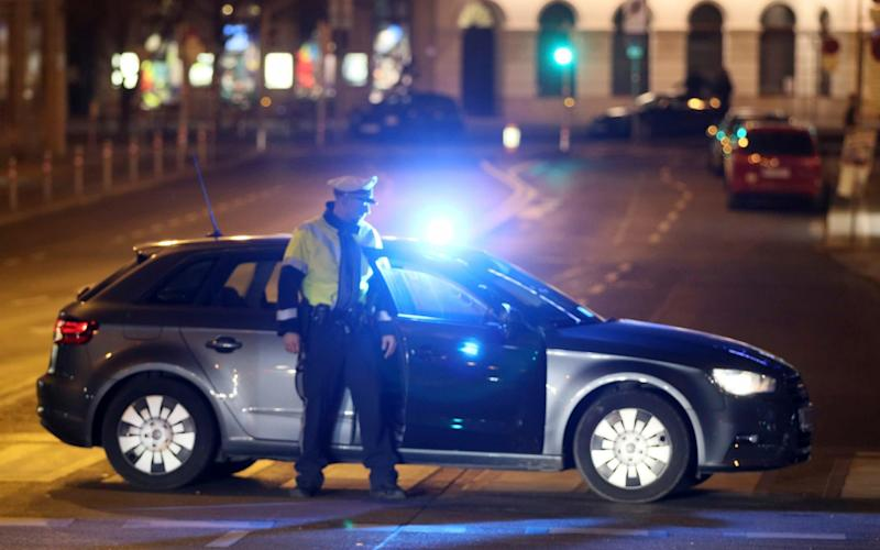 An officer blocks a street while police search for a knife attacker - AP
