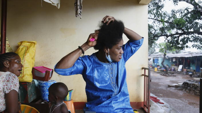 Guinean wrestler Fatoumata Yarie Camara combs her hair at her house in Conakry, Guinea, Wednesday July 21, 2021. A West African wrestler's dream of competing in the Olympics has come down to a plane ticket. Fatoumata Yarie Camara is the only Guinean athlete to qualify for these Games. She was ready for Tokyo, but confusion over travel reigned for weeks. The 25-year-old and her family can't afford it. Guinean officials promised a ticket, but at the last minute announced a withdrawal from the Olympics over COVID-19 concerns. Under international pressure, Guinea reversed its decision. (AP Photo/Youssouf Bah)