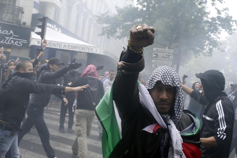 A protester wearing a kaffiyeh and wrapped in a Palestinian flag raises his fist on July 13, 2014 in Paris