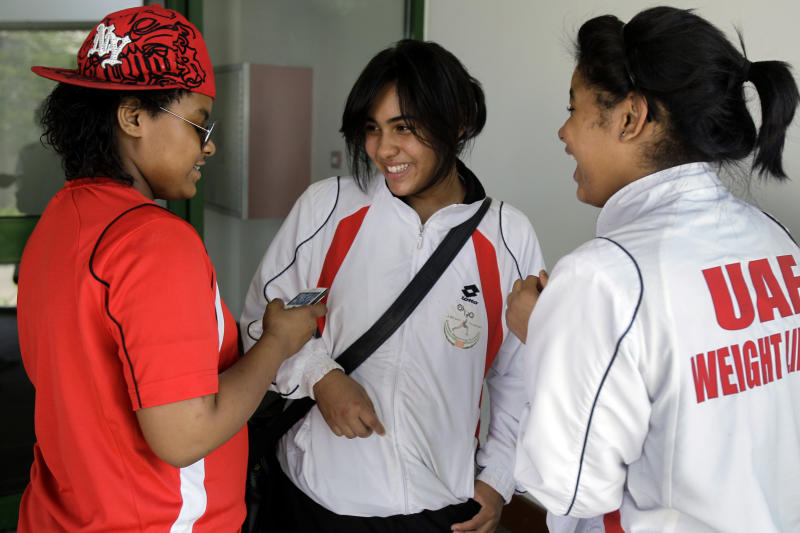 In this Monday, June 18, 2012 photo, Khadija Mohammed, left, talks to her teammates Alanood Abdulla Faraj, middle, and Abeer Abdulla Faraj at the Al Shabab stadium in Dubai , United Arab Emirates. Mohammed competes in the 75-kilogram category and will be the first female weightlifter from the Gulf at the Olympics and the first Emirati to qualify for the Olympics outright. (AP Photo/Kamran Jebreili))